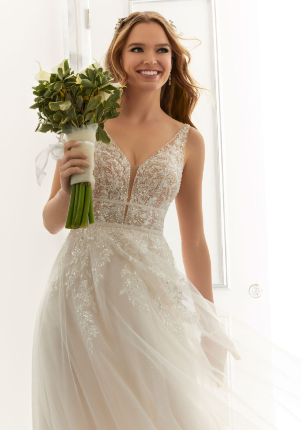 Pearl and crystal beaded embroidery add dreamy sparkle and dimension to the V-neck bodice of our Angela wedding dress