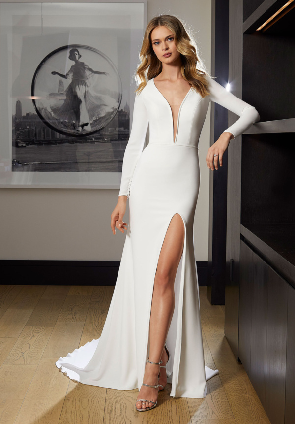 The plunging neckline, with sheer inset, and skirt slit add seductive elements to this sleek gown.