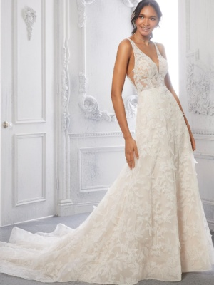 Featuring three-dimensional, allover floral lace, the sheer v-neck bodice leads to an open keyhole back, while the soft A-line skirt cascades down the body to the wide horsehair hemline.